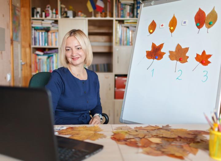 Woman teaching fall-themed lesson to students on laptop